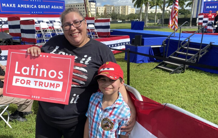"""Amera Franklin holds a """"Latinos for Trump"""" sign with her 7-year-old son at a park."""