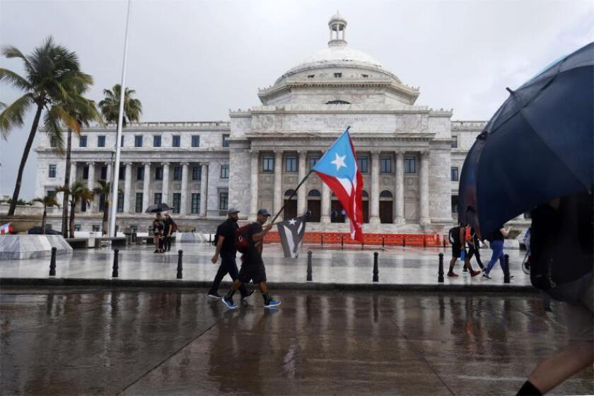 Unas personas con banderas nacionales caminan frente al Capitolio, de la Cámara de Representantes y el Senado, este lunes en San Juan (Puerto Rico). EFE/Thais Llorca