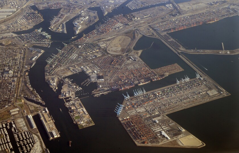 The sprawling Port of Los Angeles is seen from a commercial jetliner. A group of warehouse workers at the port is suing a major distribution company for back pay.