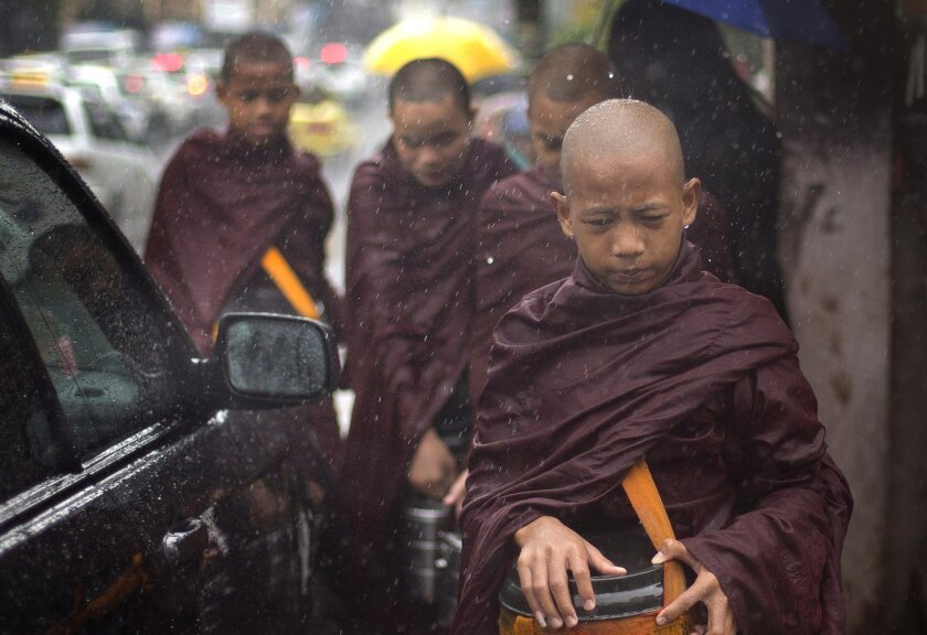 Novice Buddhist monks walk to collect alms in the rain following a cleric's rule of no footwear nor use of umbrellas on a street of Yangon, Myanmar, Thursday, July 31, 2014. Downpours during the monsoon season are intense, and often more than 100 millimeters (3.9 inches) of water falls in an hour resulting flash floods and traffic jams. (AP Photo/Gemunu Amarasinghe)