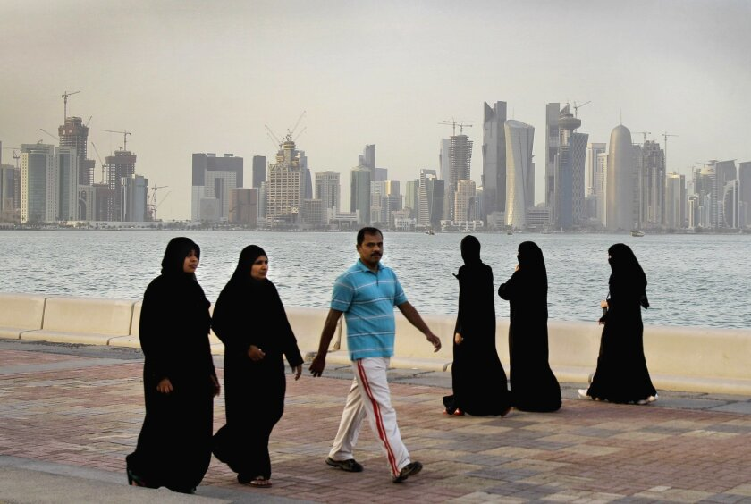 FILE- In this Saturday, April 7, 2012 file photo, with the new high-rise buildings of downtown Doha, background, Qatari women and a man walk by the sea in Doha, Qatar. The economic slowdown gripping countries across the Persian Gulf can be seen in layoffs, slowed construction projects and governmen