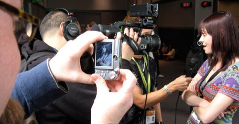 """'EXTREMELY META': A conference attendee takes a photo of Mahalo Daily host Veronica Belmont, who's being interviewed by Brian Tong of CNet TV. """"Everyone's a maker,"""" Belmont says."""