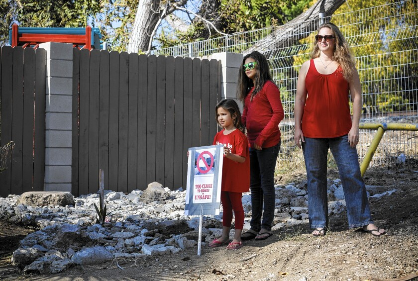 Leah Guardino, 5, left, her sister Ava and mother Briana oppose Metro's plan to build a new track on an existing right of way near their Northridge home. About 130 homes are directly adjacent to the tracks.