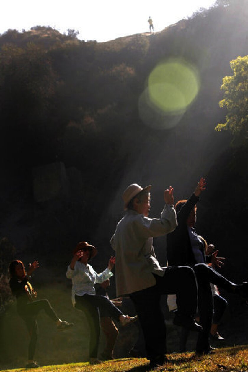 Kiki Kiko, center in hat, of Studio City, joins others to practice tai chi in Griffith Park's Bronson Canyon Park.