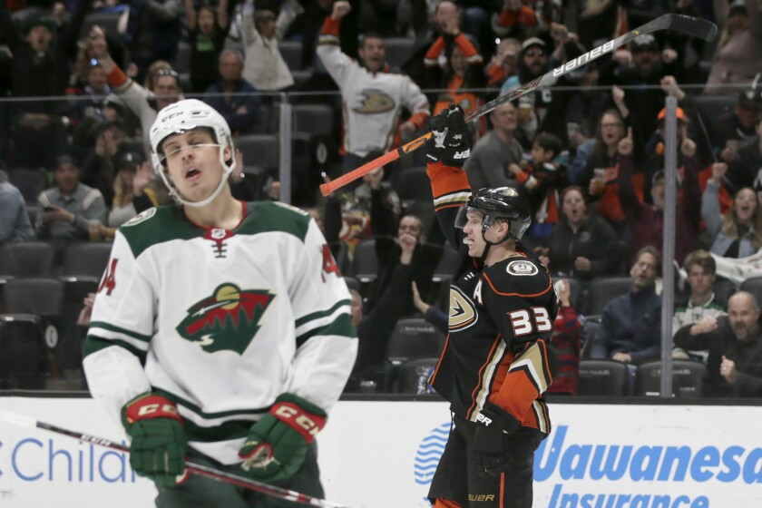 Anaheim Ducks right wing Jakob Silfverberg, right, of Sweden, raises his stick in celebration, after scoring a goal, as Minnesota Wild center Joel Eriksson Ek, left, of Sweden, laments during the second period of an NHL hockey game in Anaheim, Calif., Sunday, March 8, 2020. (AP Photo/Alex Gallardo)