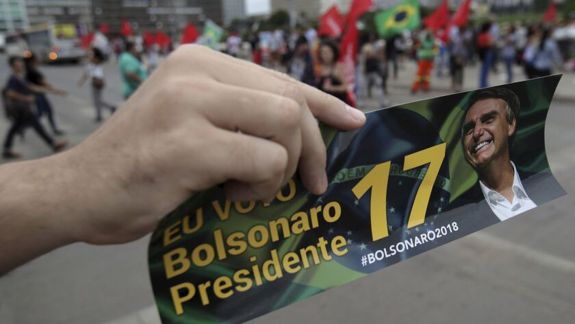 A supporter of presidential front-runner Jair Bolsonaro holds up a bumper sticker promoting her candidate during a campaign rally in Brasilia, Brazil, Wednesday.