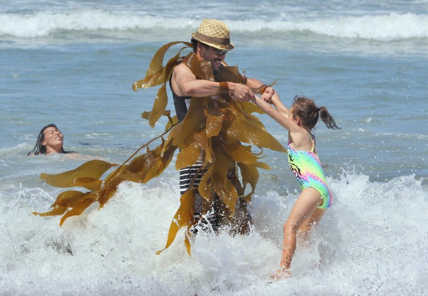 Daniel Burrola covered himself with kelp as he swings friend Kiera Milligan at Mission Beach.