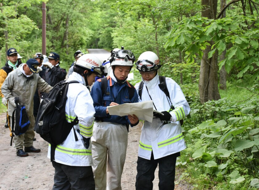 Rescuers search for a 7-year-old boy who is missing in a Japanese forest in Nanae town, on Hokkaido, the northernmost of Japan's four main islands, on Monday, May 30, 2016.