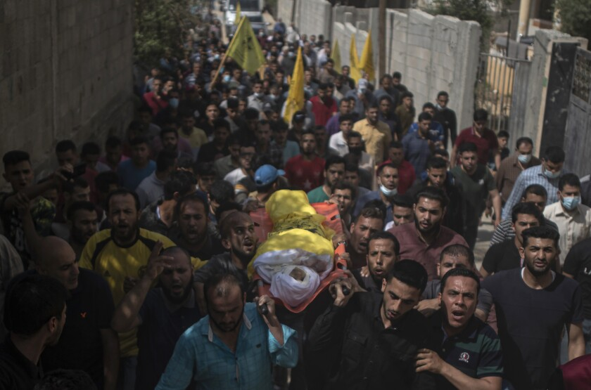 Mourners carry a body wrapped in white and yellow amid a throng of people
