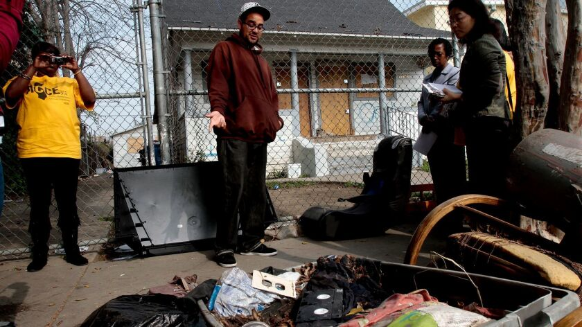A foreclosed home on East 48th Street in Los Angeles is highlighted during a 2013 tour by the Alliance of Californians for Community Empowerment and other organizations.