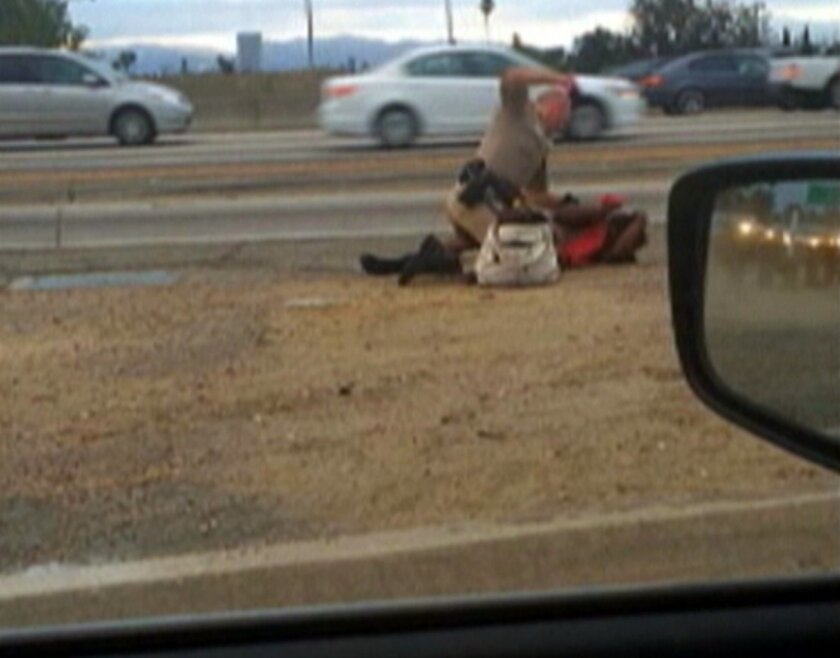 In this July 1, 2014 image made from video provided by motorist David Diaz, a California Highway Patrol officer straddles a woman while punching her in the head on the shoulder of a Los Angeles freeway. The woman had been walking on Interstate 10 west of downtown Los Angeles, endangering herself and people in traffic, and the officer was trying to restrain her, according to a CHP assistant chief. The officer, who has not been identified, has been placed on administrative leave during an investigation. (AP Photo/David Diaz)
