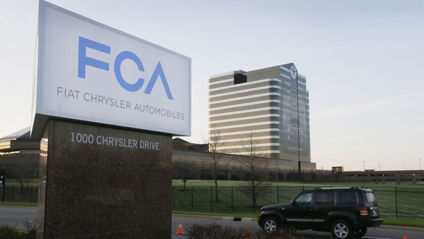FILE - In this May 6, 2014, file photo, a vehicle moves past a sign outside Fiat Chrysler Automobile