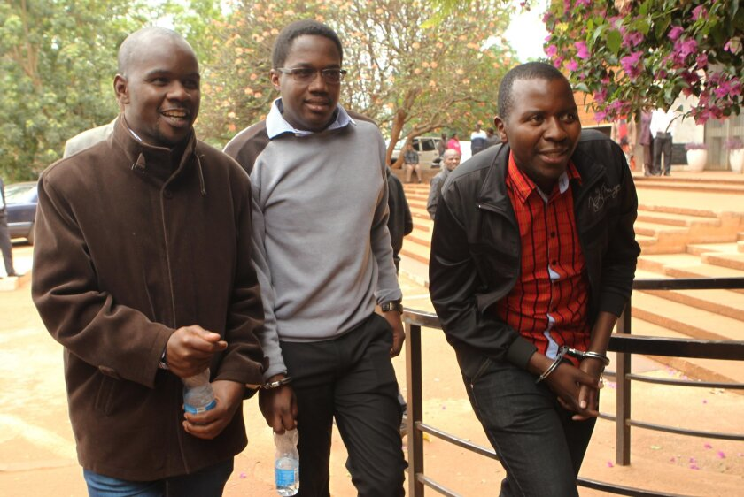 Zimbabwean journalists Brian Chitemba, left, Mabasa Sasa, centre, and Tinashe Farawo walk in handcuffs, outside the magistrates courts in Harare, Zimbabwe, Wednesday, Nov. 4.2015. A Zimbabwean court has granted bail to three journalists accused of slander after they allegedly implicated an unnamed