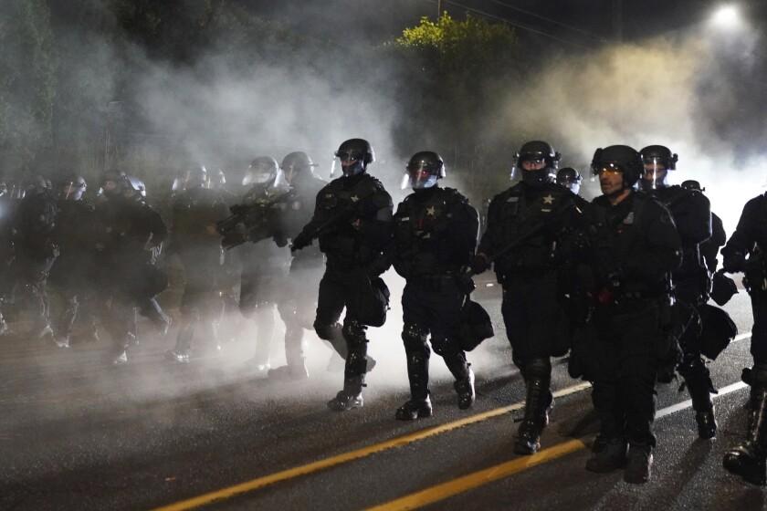 Los agentes de la policía de Portland avanzan por el vecindario de Laurelhurst