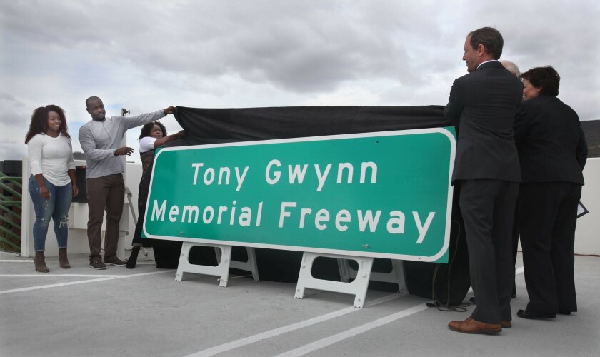 From left, Anisha Gwynn Jones, her brother Tony Gwynn Jr., and their mother Alicia Gwynn help unveil the new freeway signs honoring their late father. At right are Assemblyman Brian Maienschein and Laurie Berman, director of Caltrans Distric 11. Supervisor Ron Roberts is not visible behind the other two on right. On Monday the late Tony Gwynn's wife Alicia and his two children Anisha Gwynn Jones and Tony Gwynn Jr. joined California State Assemblyman Brian Maienschein, County Supervisor Ron Roberts and Laurie Berman, director of Caltrans District 11 to unveil the new freeway signs memorializing the athlete who many remember as much for his community involvement as his unparalleled athletic feats. The signs will be posted along the stretch of Interstate 15 near the intersection with Ted Williams Parkway in north county where the Gwynns live.