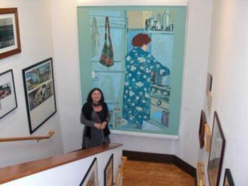 Erika Torri, executive director of the Athenaeum Music & Arts Library, stands by 'Mary at the Stove' by Patricia Patterson. The painting hangs on a moveable piece of plaster wall. Linda Hutchison