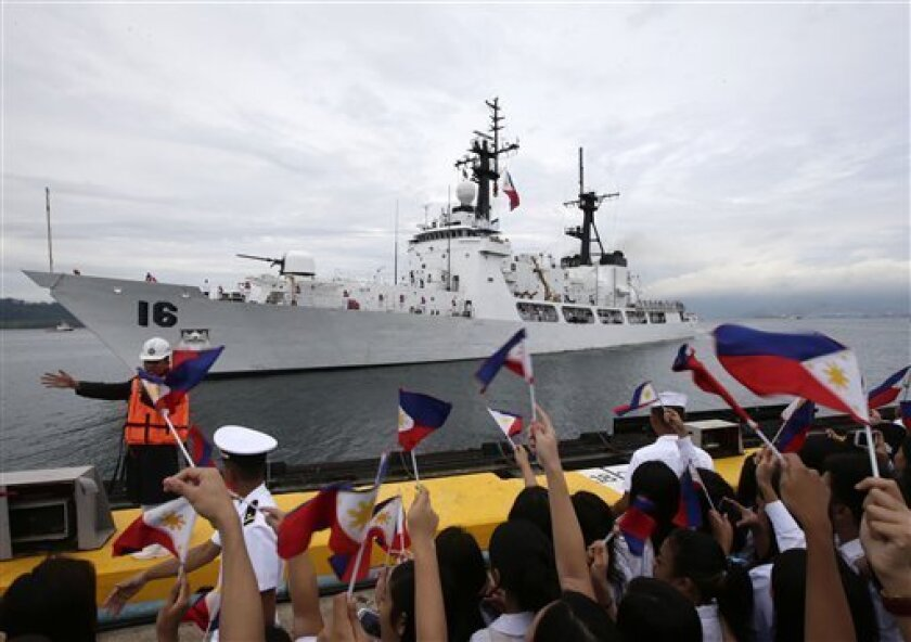 Students and other guests wave Philippine flags to welcome the second warship of the Philippine Navy, the BRP Ramon Alcaraz Tuesday, Aug. 6, 2013 at Subic Freeport, about 80 kilometers (50 miles) northwest of Manila, Philippines. The Philippines on Tuesday celebrated the arrival of its second major warship to challenge China's massive territorial claims in the South China Sea that Filipino officials say have intruded into their country's potentially oil-rich offshore territory. (AP Photo/Bullit