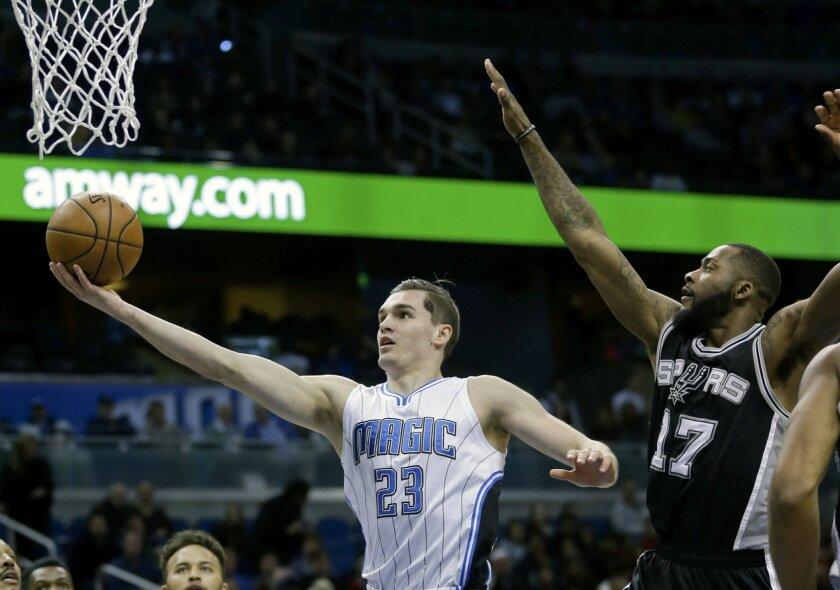 Orlando Magic guard Mario Hezonja (23) gets past San Antonio Spurs guard Jonathon Simmons (17) for a basket during the first half of an NBA basketball game, Wednesday, Feb. 10, 2016, in Orlando, Fla. (AP Photo/John Raoux)