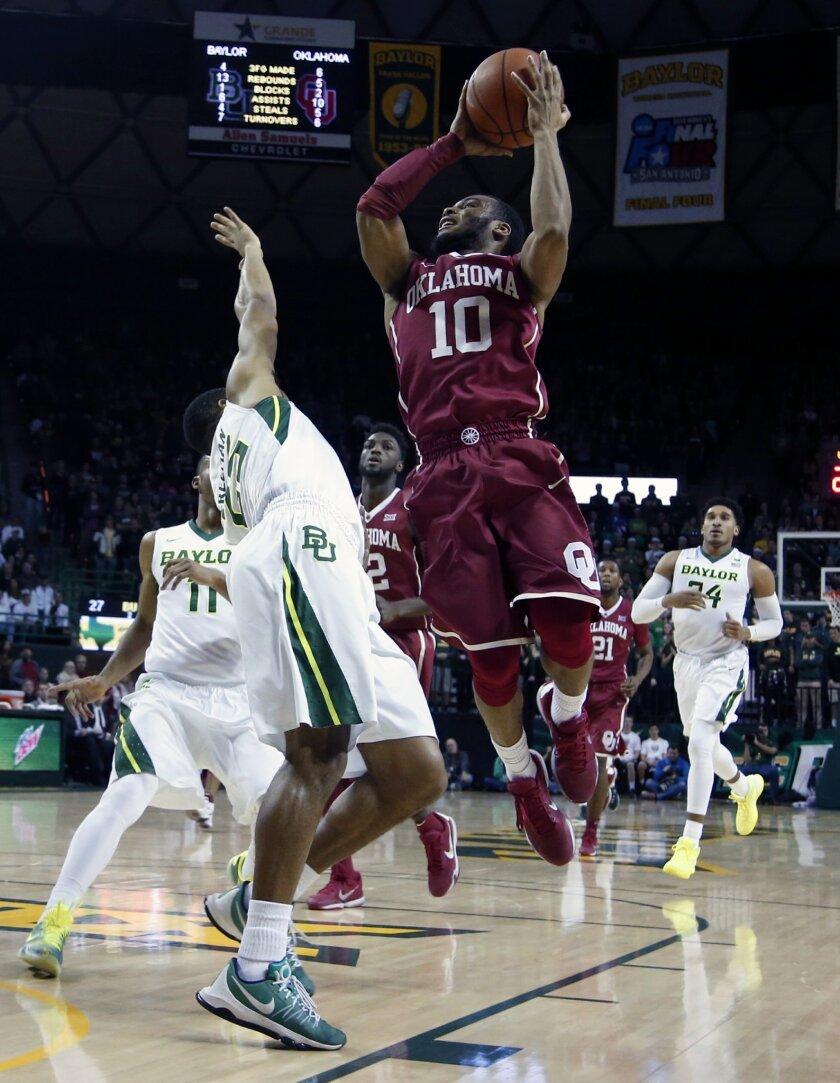 Oklahoma guard Jordan Woodard (10) scores over Baylor guard Al Freeman (25) in the first half of an NCAA college basketball game, Saturday, Jan. 23, 2016, in Waco, Texas. (AP Photo/Rod Aydelotte)