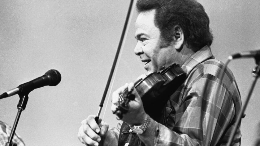 FILE - In this June 27, 1983, file photo, entertainer Roy Clark plays the fiddle during a taping of