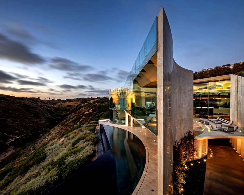 A cutting-edge blend of concrete and glass, the jagged, sweeping structure hugs the side of a cliff and takes in sweeping ocean views.