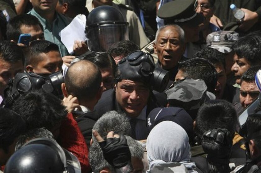 Ecuador's President Rafael Correa, center, wearing a gas mask, is caught in the middle of a police protest at a police base in Quito, Ecuador, Thursday Sept. 30, 2010.  The government declared a state of siege Thursday after rebellious police, angered by a law that cuts their benefits, shut down ai
