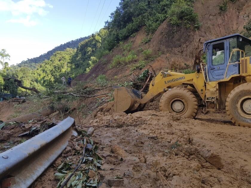 Un bulldozer despeja un camino dañado por un deslave para llegar a una aldea que quedó afectada por otro alud en la provincia de Quang Nam, Vietnam, el jueves 29 de octubre de 2020. (Bui Van Lanh/VNA via AP)