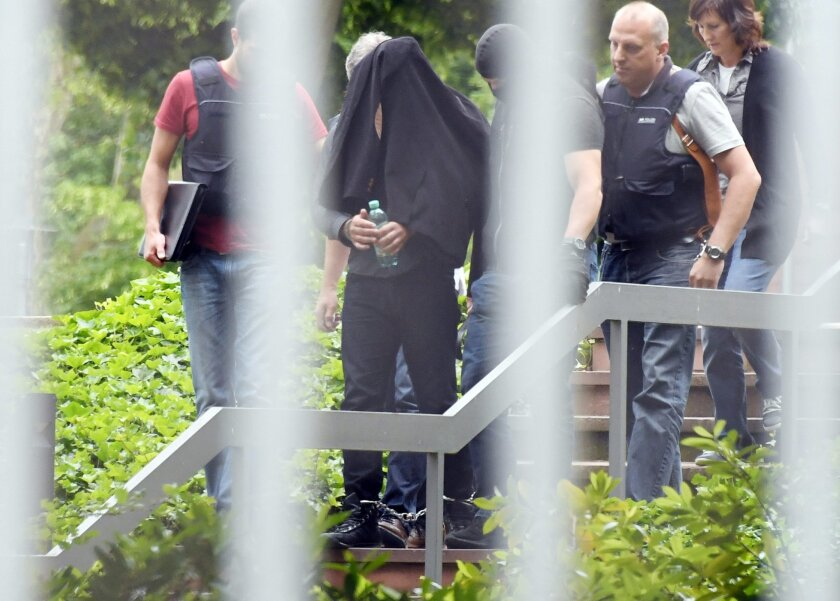 An alleged terror suspect is led by police at the Federal court in Karlsruhe, Germany, Thursday, June 2, 2016. Prosecutors said three Syrian men suspected of planning an attack in Duesseldorf for the Islamic State group have been arrested in Germany. They say a fourth suspect, who informed official