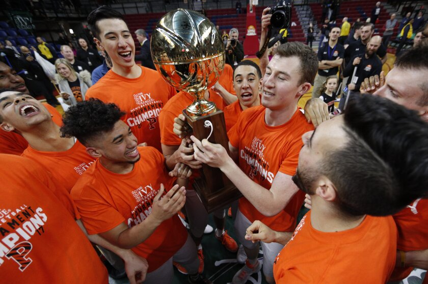 Princeton gather arounds the Ivy League Basketball Tournament Trophy following the championship game.