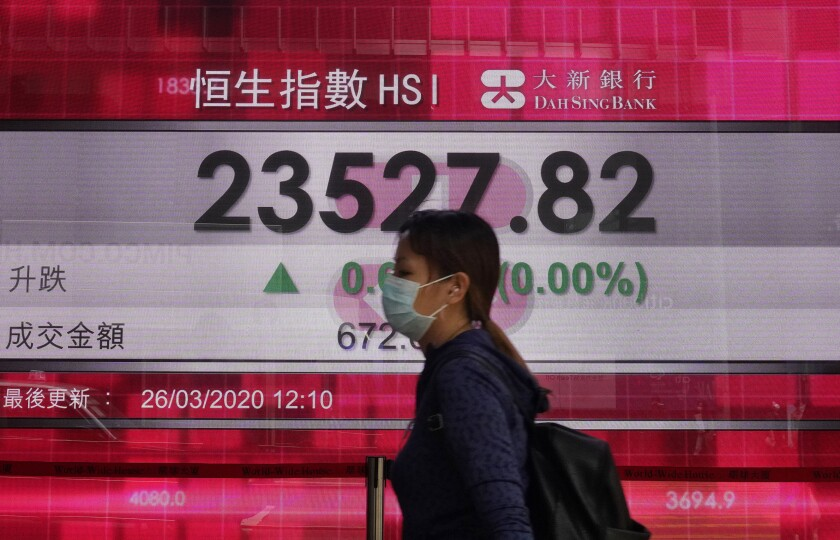 A woman walks past an electronic board at the Hong Kong Stock Exchange on March 26.