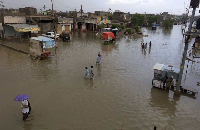 Residents wade through a flooded area caused by heavy monsoon rains, in Karachi, Pakistan, on Friday.