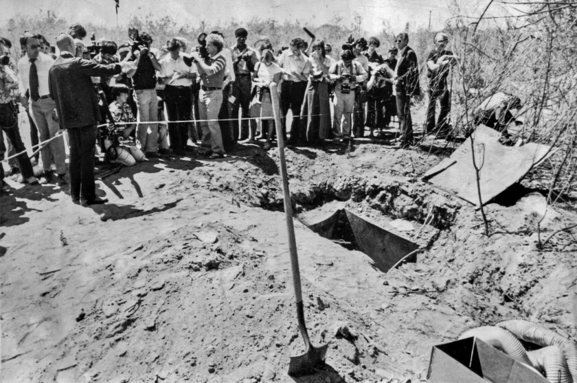 July 17, 1976: Alameda County Sheriff Tom Houchins briefs the news media at the Livermore quarry where the Chowchilla children were buried. They escaped through the shaft lower right in this photo.