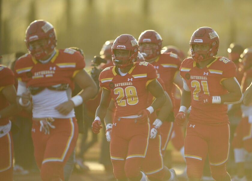 Cathedral Catholic High School football players jog onto the field
