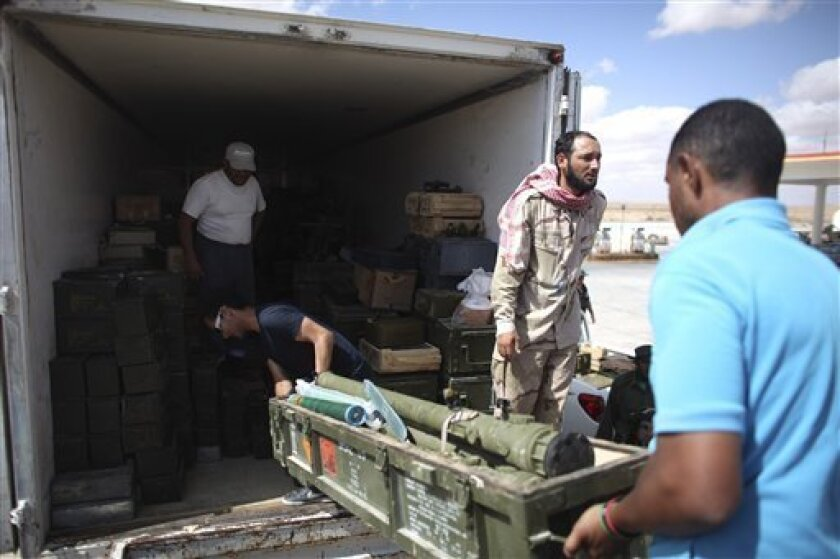 Rebels unload ammunition from a truck in Wish Tata, Libya, Friday, Sept. 9, 2011. Libya's rebels have surrounded the ousted dictator Moammar Gadhafi, and it is only a matter of time until he is captured or killed, a spokesman for Tripoli's new military council said Wednesday. (AP Photo/Alexandre Meneghini)