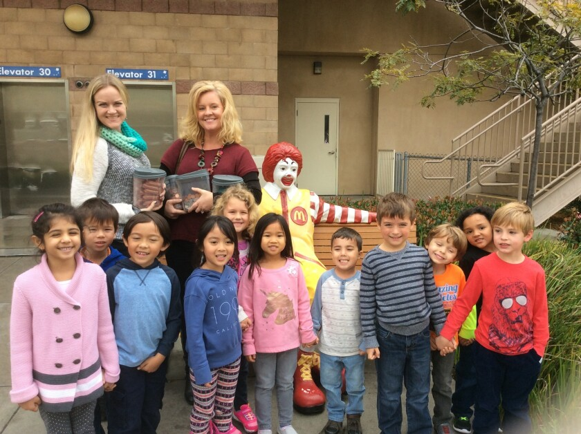 Teachers Julie Herd, left, and Stacey Loyola accompanied kindergarteners from Discovery Isle Preschool in Oceanside to donate pennies to Ronald McDonald House Charities of San Diego.