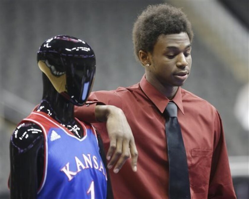 Kansas guard Andrew Wiggins stands next to a mannequin in a KUansas University uniform during Big 12 NCAA college basketball media day in Kansas City, Mo., Tuesday, Oct. 22, 2013. (AP Photo/Orlin Wagner)