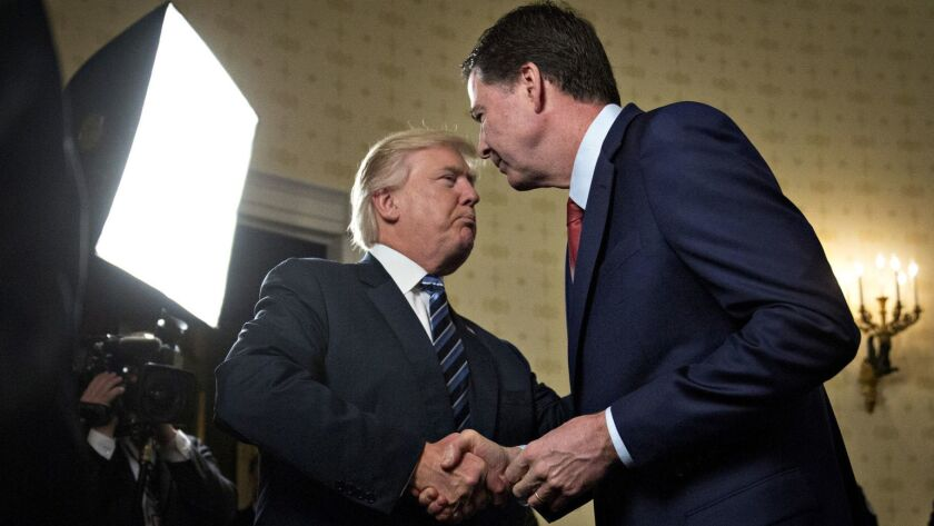 President Trump shakes hands with James Comey, then the director of the FBI, at the White House on Jan. 22, 2017.