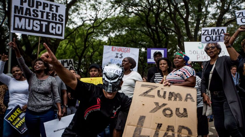 Demonstrators calling for South African President Jacob Zuma's resignation hold placards and shout s