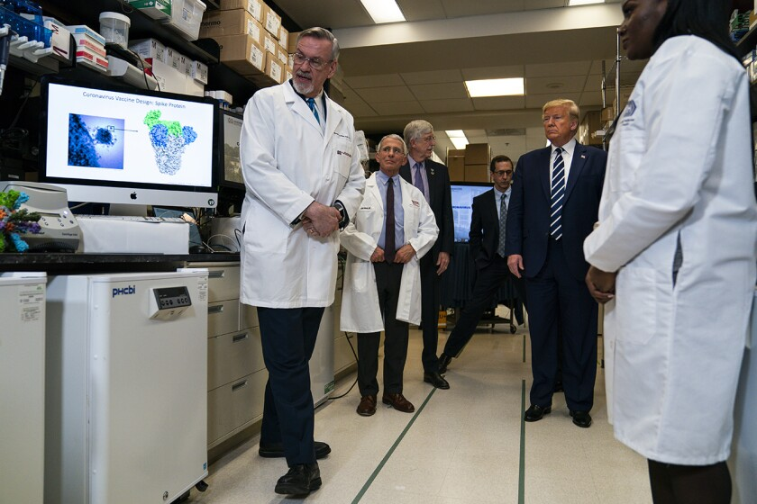 President Trump stands amid doctors in white coats in a lab.