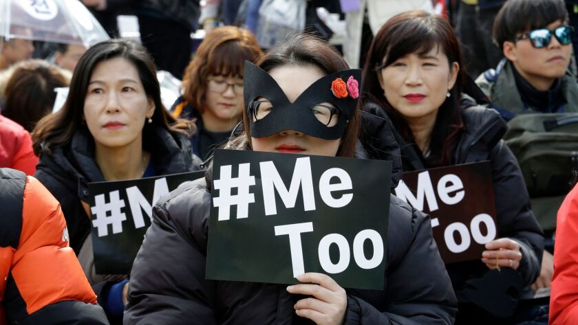 Female workers supporting the MeToo movement wearing black attend a rally to mark the International