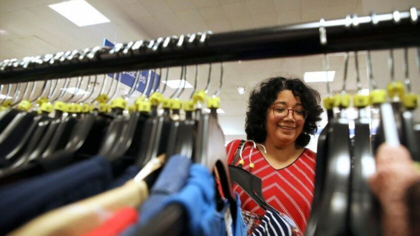 Lilie Ruiz, of Chicago, sifts through a rack of tops at Macy's Backstage in Old Orchard Shopping Center in Skokie. Macy's has seven free-standing Backstage stores in the U.S. and plans to roll out the discount section in 100 Macy's stores this year.