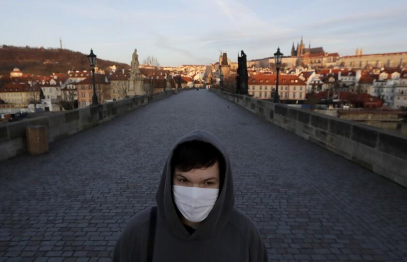 ARCHIVO - En esta imagen de archivo del 16 de marzo de 2020, un joven con mascarilla camina por el Puente Carlos en Praga, República Checa. Los checos afrontaban de nuevo estrictas medidas para contener los contagios de coronavirus, pese a las promesas del gobierno sobre que las restricciones de la primavera no volverían y ante un gran auge de los casos. (AP Foto/Petr David Josek, Archivo)