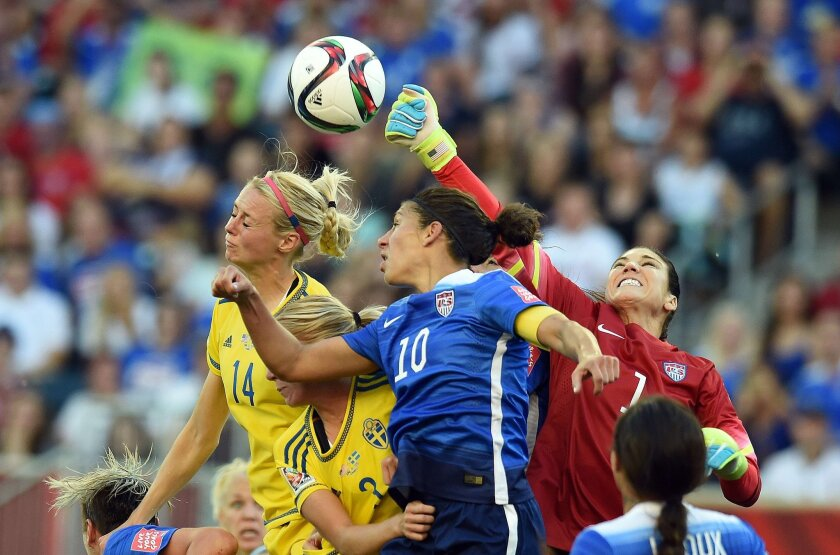 U.S. goalkeeper Hope Solo reaches in to punch the ball away as Sweden's Amanda Ilestedt (14) goes for a header and Carli Lloyd (10) does her best to help out Solo at Winnipeg.