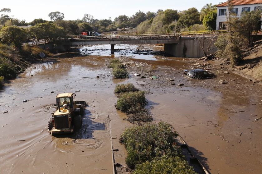 MONTECITO, CA – JANUARY 10, 2018: Crews work to clear debris from the closed 101 freeway at Oliv