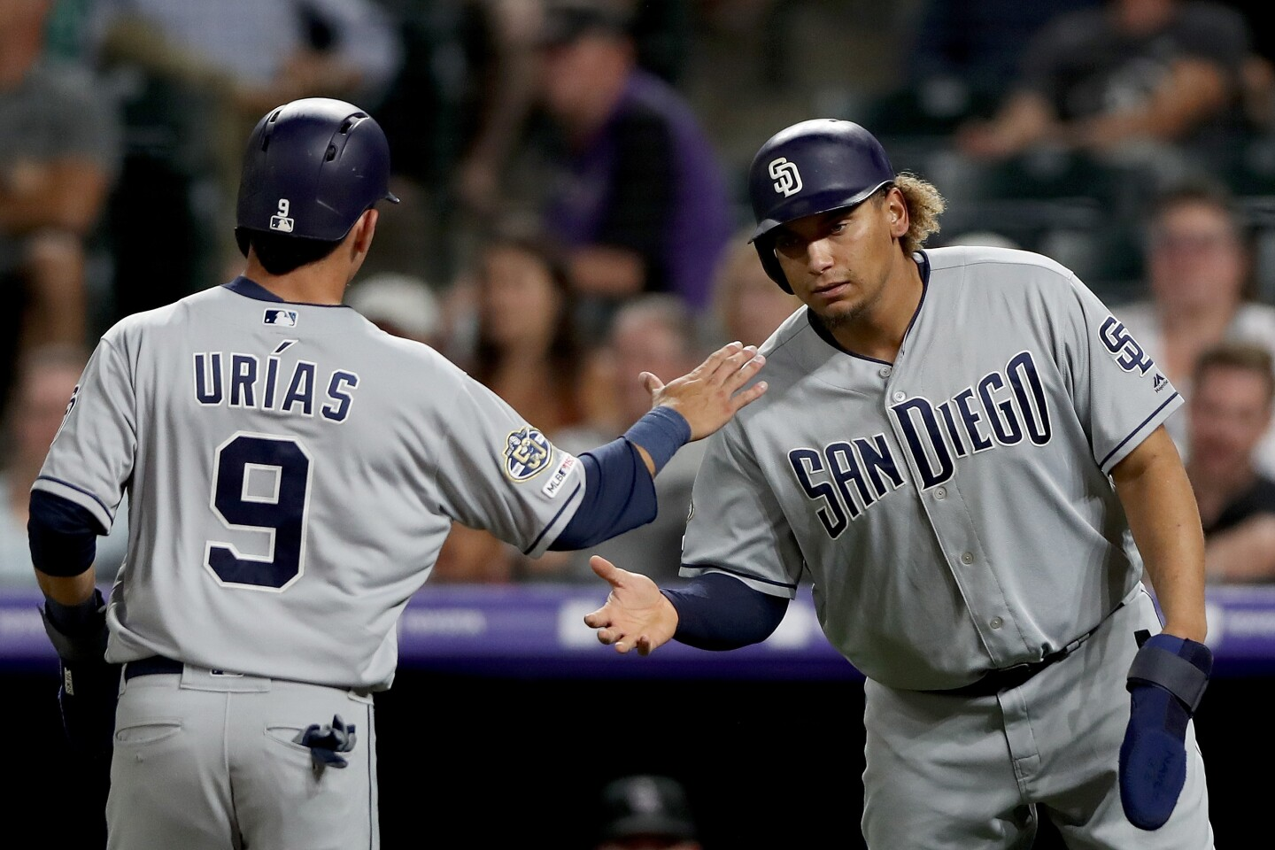 DENVER, COLORADO - SEPTEMBER 13: Luis Urias #9 of the San Diego Padres celebrates with Josh Naylor #22 after both scoring on a Ty France single in the sixth inning against the Colorado Rockies at Coors Field on September 13, 2019 in Denver, Colorado. (Photo by Matthew Stockman/Getty Images) ** OUTS - ELSENT, FPG, CM - OUTS * NM, PH, VA if sourced by CT, LA or MoD **