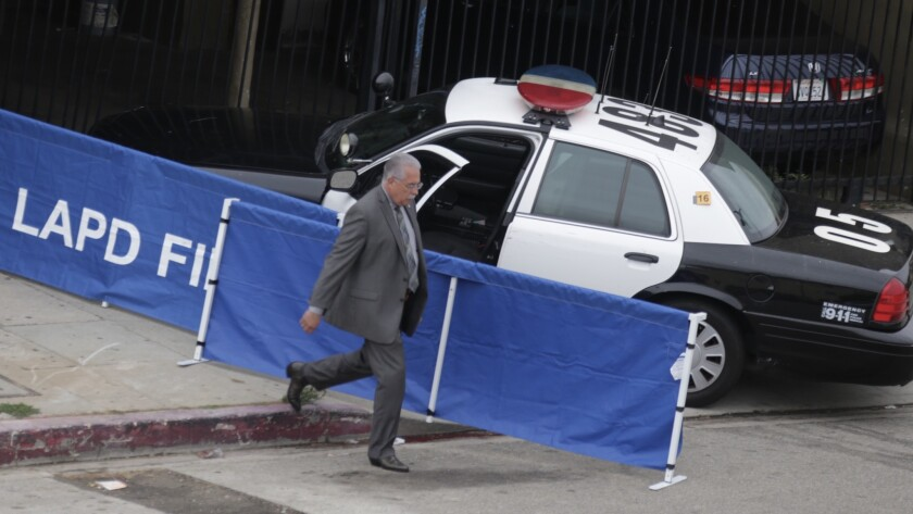An LAPD investigator cordons off a police car as part of an investigation into last week's fatal police shooting of a 20-year-old man in Wilmington. Chief Charlie Beck said that Eric Rivera fell to the ground after he was shot and was then struck by the officers' vehicle.