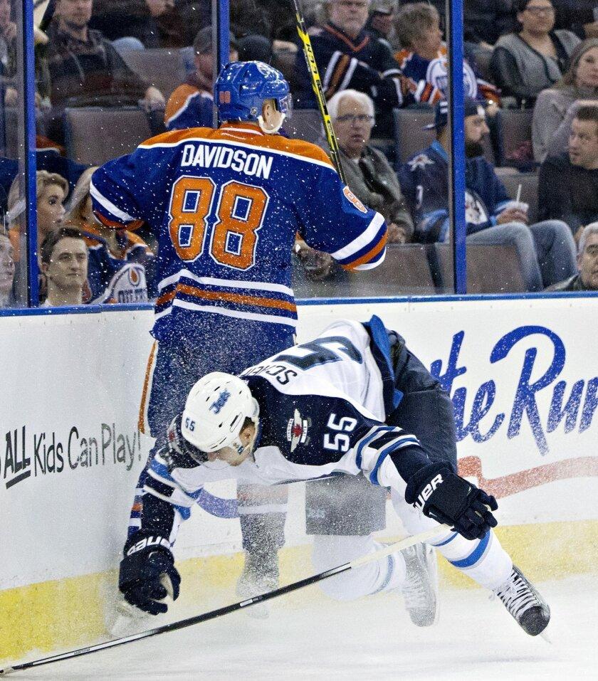 Winnipeg Jets' Mark Scheifele (55) is checked by Edmonton Oilers' Brandon Davidson (88) during the first period of an NHL hockey game Saturday, Feb. 13, 2016, in Edmonton, Alberta. (Jason Franson/The Canadian Press via AP)