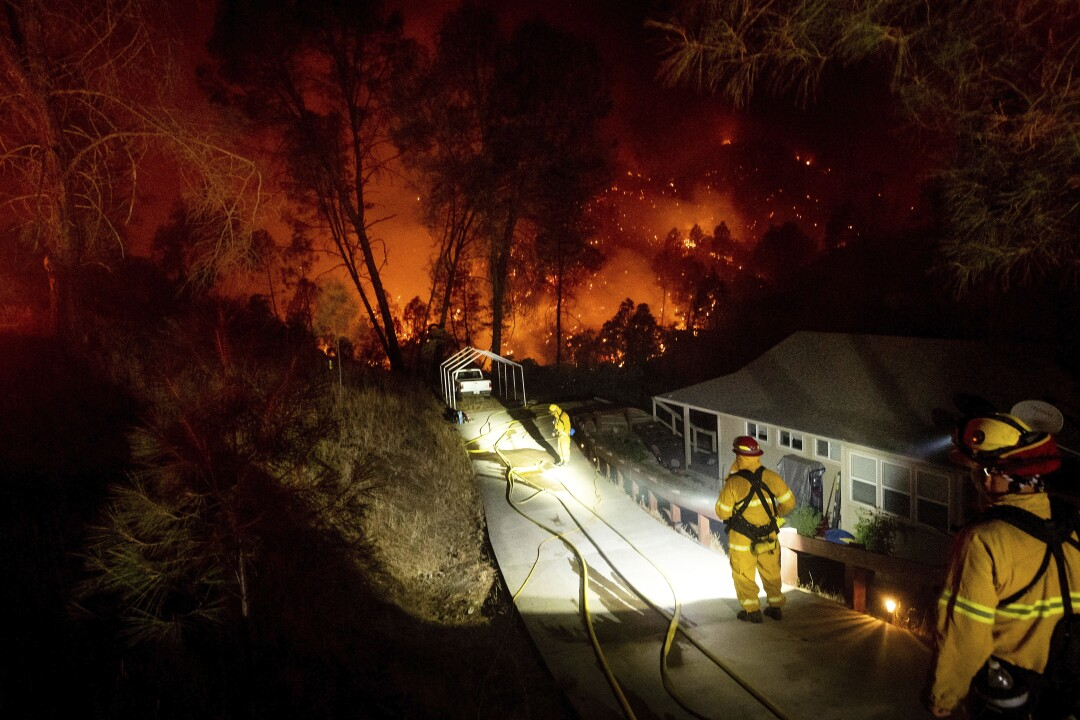 Firefighters protect a home in the Berryessa Estates neighborhood of unincorporated Napa County.