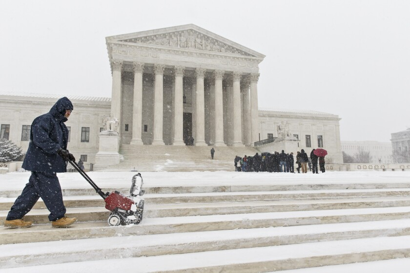 A worker clears snow from the plaza at the Supreme Court in Washington on March 3 as those waiting to hear oral arguments line up.