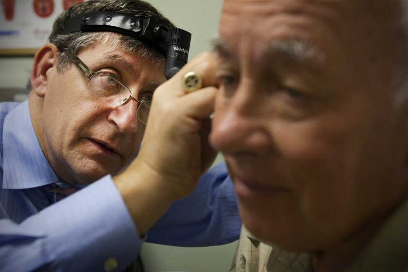 Dr. Ted Mazer examines the ear of his patient, Victor Sontuvoi at his office in San Diego in 2011. Mazer worked with a team of medical leaders across the state to increase Medicare reimbursement for local doctors.